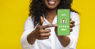 Unrecognizable Black Woman Pointing At Smartphone With Rating Application On Screen