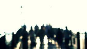 Unrecognizable blurred people walking. 4K bokeh shot. Back light stock video footage