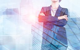 Unrecognizable boss woman in city. Unrecognizable confident businesswoman standing with crossed arms over abstract skyscrapers background. Leadership concept royalty free stock image