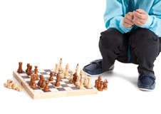 Unrecognizable boy playing chess, sitting behind wooden chessboard, isolated white background Royalty Free Stock Photos