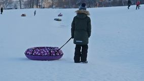 Boy with sled on a snow hill. Unrecognizable boy with sled on a snow hill walking by with sleds slow motion stock video footage
