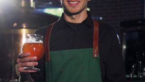 Unrecognizable brewer in apron showing thumbs up, holding glass of beer stock photos