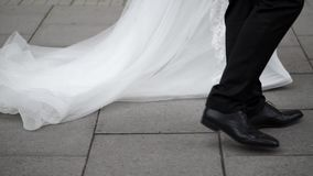 Unrecognizable bride and groom walking on a street. At cloudy day stock footage