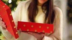 Unrecognizable Brunette Opening Christmas Gift, Indoors. Unpacking the Red Box with Present. Blurred Xmas Lights on stock video footage