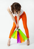 Unrecognizable brunette in orange pants holding shopping bags Stock Photography