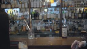 Unrecognizable brunette woman and blond bearded man sitting at the bar counter close up. Concept of night lifestyle. Cute couple has a date. Back view. Camera stock footage