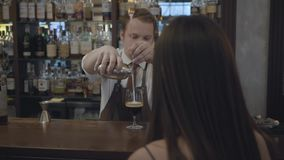 Unrecognizable brunette woman sitting at the bar counter. Plump bartender pouring two portions of espresso in the glass. Unrecognizable brunette woman sitting at stock footage