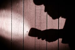 Unrecognizable burglar with  flashlight  in shadow on wood backg Stock Photos