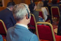 business people using headphones for translation during event . bald security guard with the headset to control peo stock photography