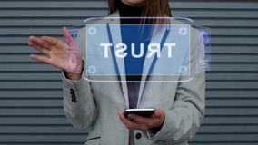 Business woman interacts HUD hologram Trust. Unrecognizable business woman, interacts with a HUD hologram with text Trust. Girl in a business suit uses the stock footage