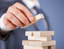 Unrecognizable businessman forming a wooden pyramid Stock Images