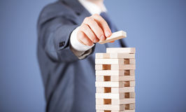 Unrecognizable businessman forming a wooden pyramid Stock Photography