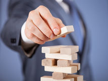 Unrecognizable businessman forming a wooden pyramid Stock Image