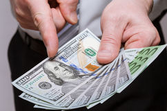 Unrecognizable businessman holding dollars and euro Stock Photos