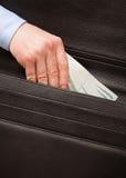 Unrecognizable businessman puts money in a briefcase Stock Photo