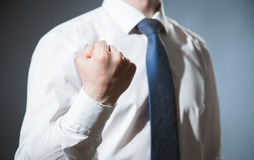 Unrecognizable businessman showing a strong fist. Dark background Stock Photo