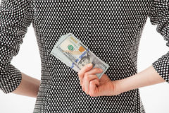 Unrecognizable businesswoman hiding money behind back Stock Image