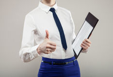 Unrecognizable businesswoman holding documents and showing thumb Stock Image