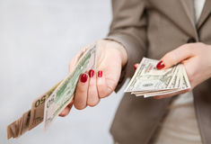 Unrecognizable businesswoman holding dollars. Neutral background Stock Images