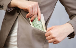 Unrecognizable businesswoman holding dollars. Neutral background Royalty Free Stock Photography