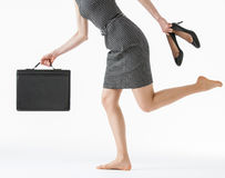 Unrecognizable businesswoman running and holding her shoes and a Royalty Free Stock Images