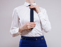 Unrecognizable businesswoman sets the necktie Royalty Free Stock Photography