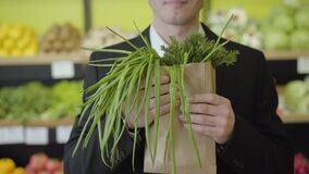 Unrecognizable Caucasian man smelling dill and green onion in paper pack and stretching bunch of greenery to camera
