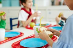 Kids eating lunch at school. Unrecognizable children sitting at table and eating tasty sandwiches while having lunch in elementary school canteen stock images