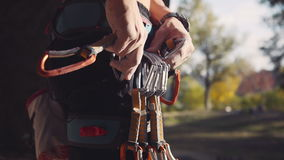 Unrecognizable climber wearing carabiners. Close-up of male climber attaching carabiners on safety belt. Mountaineer or rock climbing holding a carabiner for his stock video footage