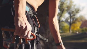 Unrecognizable climber wearing carabiners. Slowmotion of male climber attaching carabiners on safety belt. Mountaineer or rock climbing holding a carabiner for stock footage