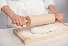 Unrecognizable cook's hands rolling out dough Stock Photography