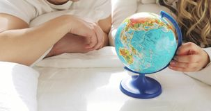 Unrecognizable couple in bed are looking at globe spinning it and pointing at random choosing a place to travel. stock video footage