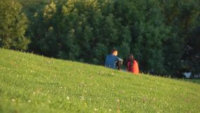Unrecognizable couple in blue and red clothes having picnic in city park. 4K long shot. Unrecognizable couple having picnic in city park. 4K shot stock footage