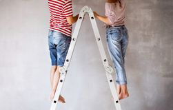 Unrecognizable couple painting walls in their house. Unrecognizable young couple standing on ladder painting walls in their new house. Home makeover and Royalty Free Stock Photo