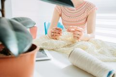 Unrecognizable craftswoman knitting something with crochet in cozy workplace at home interior. Female working with tender lace. stock image