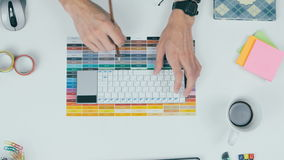 Unrecognizable creative designer working with colors on his workplace. Top view. stock footage