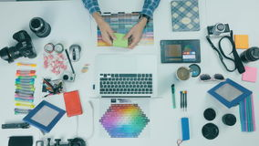 Unrecognizable creative designer working in a creative agency. Top view. 4K stock footage