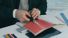 Unrecognizable creative designer working in modern office. Cutting sheets, choosing colors. Close up. stock footage