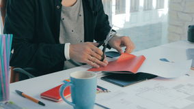 Unrecognizable creative designer working in modern office. Cutting sheets, choosing colors. Close up. stock video