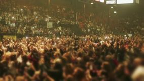 Unrecognizable crowd of people at a concert seen on the stands and the floor area. Shot of unrecognizable crowd of people cheering at a concert.  You can also stock video