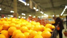 Unrecognizable customers in supermarket choose oranges. Clip stock video footage