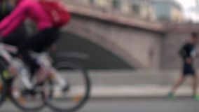 Unrecognizable defocused cyclists and runners. Activity concept. Slow motion background bokeh shot. Defocused runners. Slow motion background bokeh video stock video