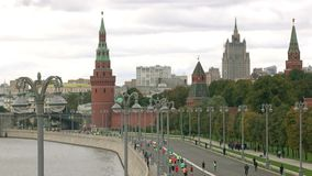 Unrecognizable distant marathon runners near Moscow Kremlin. 4K shot stock video footage