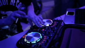 Unrecognizable Dj hands playing music at the nightclub. Mixing console. Close up. stock footage