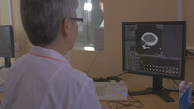 Unrecognizable Doctor examines a head MRI scan on a computer screen. stock video footage