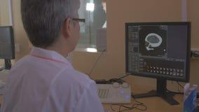Unrecognizable Doctor examines a head MRI scan on a computer screen. Doctor examines a head MRI scan on a computer screen. 4K stock video footage