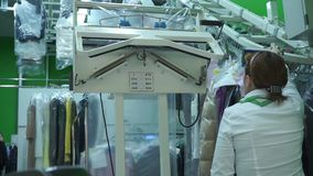 Unrecognizable dry-cleaning operator at work. Clip stock footage