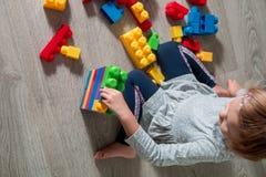 Unrecognizable dziecko dziewczyna ma zabawę i budowę jaskrawi plastikowi budowa bloki Berbeć bawić się na podłoga rozwijać zabawk Fotografia Stock