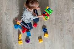 Unrecognizable dziecko dziewczyna ma zabawę i budowę jaskrawi plastikowi budowa bloki Berbeć bawić się na podłoga rozwijać zabawk Zdjęcia Stock