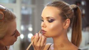 Unrecognizable fachowy makeup artysta stosuje pomadkę używać specjalnego obrazu muśnięcie na wzorcowych ` s wargach Wargi glosa zbiory
